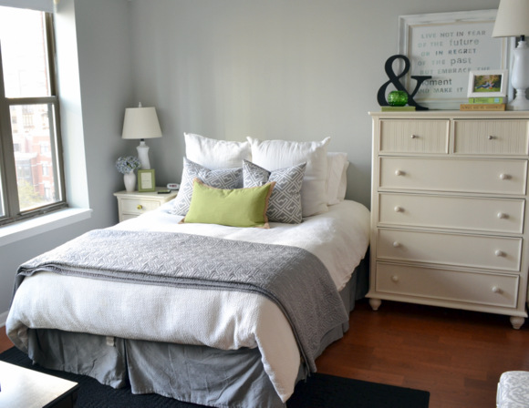 Master bedroom decorated in whites and grays with pops of green.
