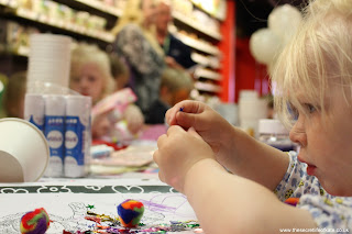 Toddler carefully applying sequins to a craft project