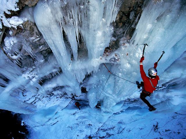 Homme escaladant une montagne enneigée.