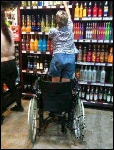 Chica en silla de ruegas comprando alchohol.