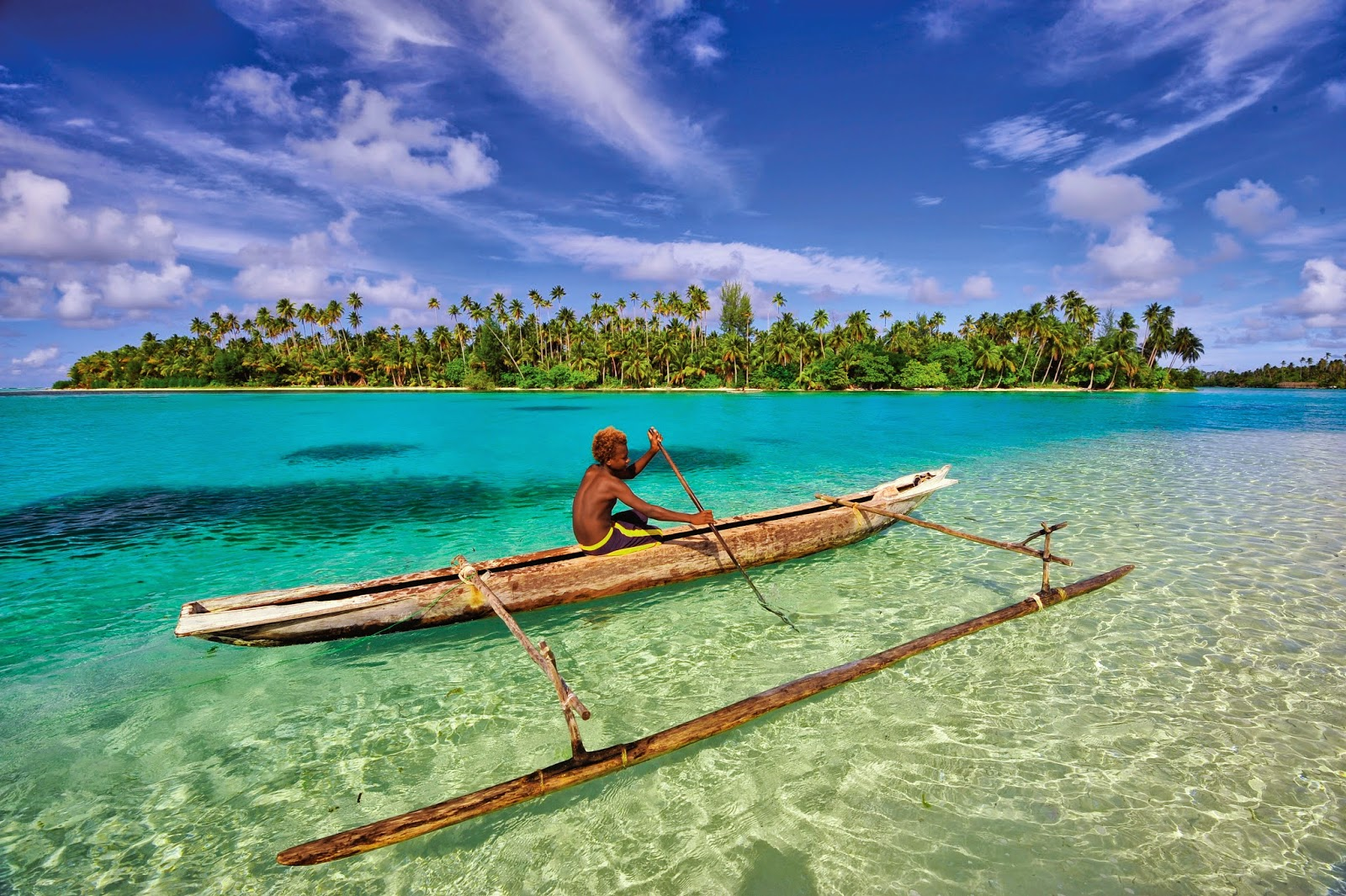 A boy canoeing in crystal clear water - Papua New Guinea