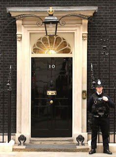 Police officer standing guard at the main doorway of Number 10