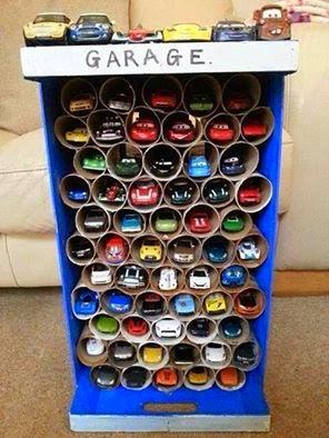 garaje para coches hecho con caja de madera y tubos de papel higienico