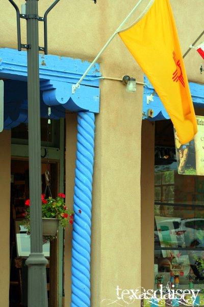 New Mexico Flag Flying near Light Blue pillar