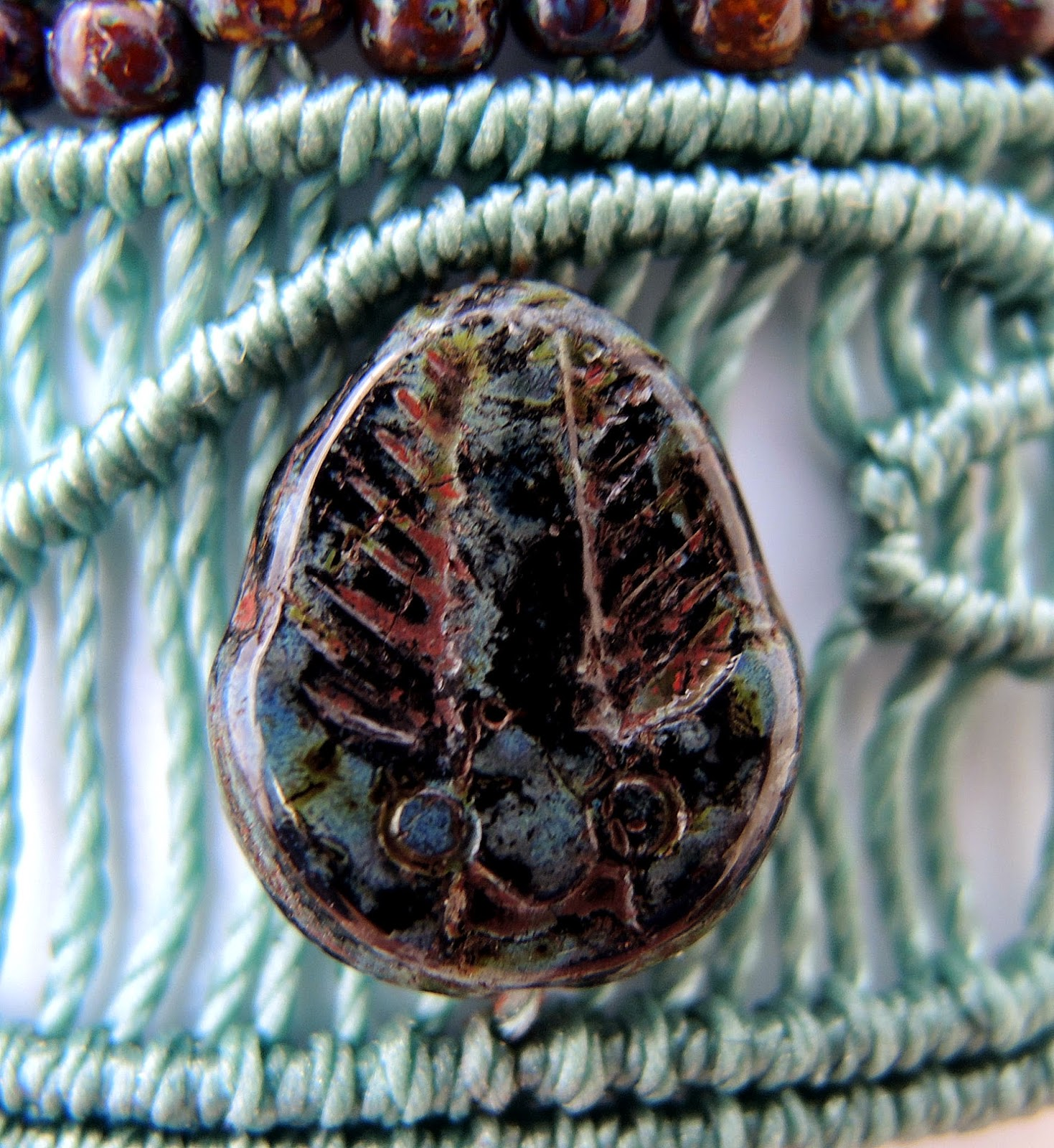 Czech glass trilobite bead set in micro macrame.