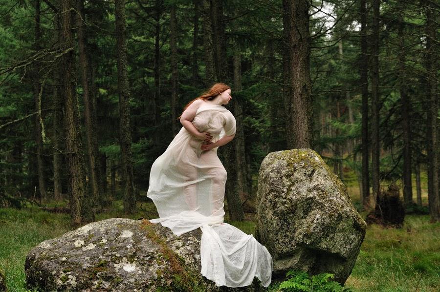 femme nue drapée dans un long voile blanc debout sur un rocher