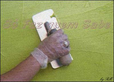 Com uma desempenadeira de aço, aplicar uma camada de textura em toda a parede