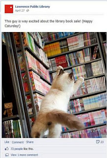 "Screen-capture of Facebook post by Lawrence Public Library, a cat reaching for shelves of books, The caption reads: ""This guy is way excited about the library book sale! (Happy Caturday!)"