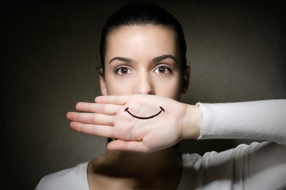Mujer triste fingiendo sonrisa
