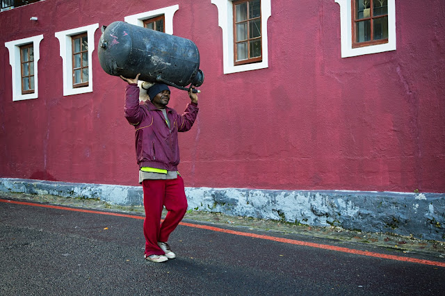 A man carries a hot water heater. He is dressed in purple against a purple wall