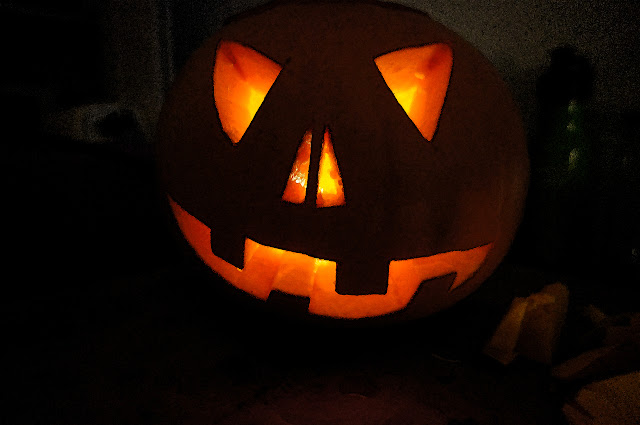 Picture of a Jack O Lantern with a candle lit inside it.