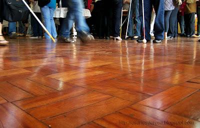 Fotografia de pernas e pés de homens e mulheres, conduzindo algumas bengalas, sobre um piso brilhoso com reflexos de suas imagens. Feita no hall da UNIOESTE, em Cascavel, PR, durante o XII Encontro Nacional de Usuários DOSVOX, em outubro de 2010.