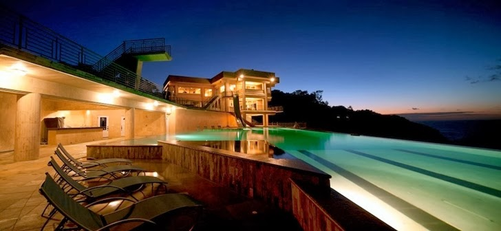 terrace and swimming pool lights in an impressive waterfall house in hawaii