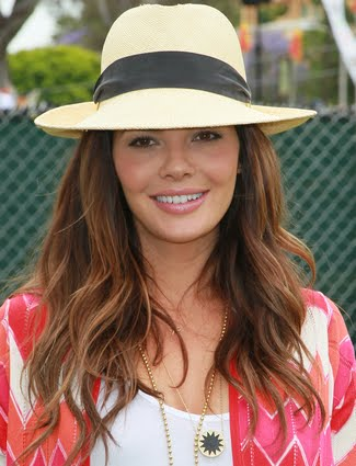 Ali Landry tops off her loose wavy hairstyle with a stylish summer hat