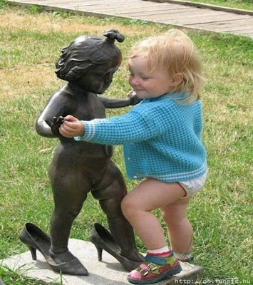 little girl dancing with statue