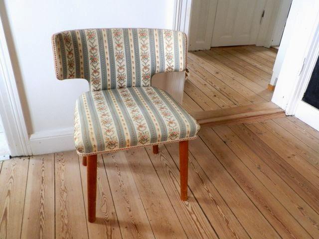 Stolen har runde koniske ben og buet ryg. Betraekket er i r?de og ...