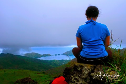 A girl meditating at the peak of mountain Cinco Picos overlooking the sea Silanguin Cove hover_share