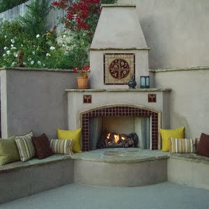 Outdoor living area with a fireplace featuring a ceramic tile Pomegranate mural