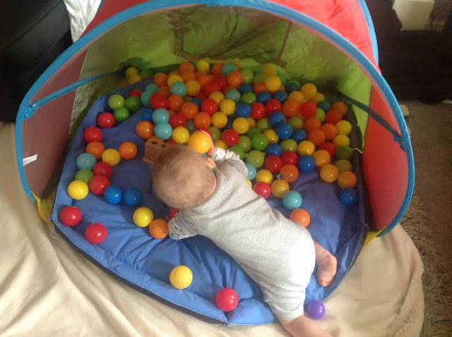 baby in tent with lot of different coloured balls