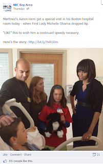 Michelle Obama visits a child and the child's family in a hospital. The child is in bed; his family stands next to him, along with Michelle Obama.