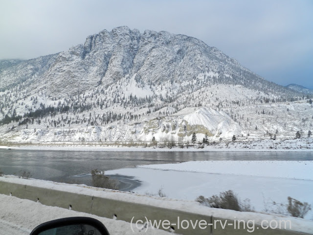 Snowy mountain is the backdrop from the highway across the river.