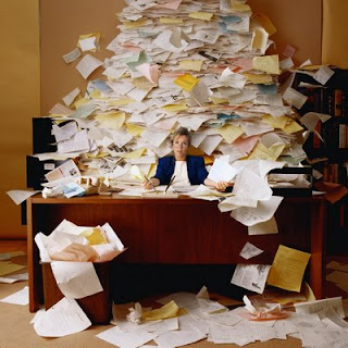 This is a picture with a person in the middle and the room filled with piles of paper!