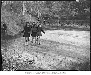 old black and white picture of five girls in skates on a frozen pond smiling for the camera