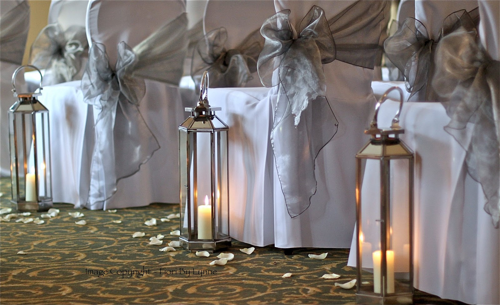 candles lit matching chair covers and sashes by the wedding project