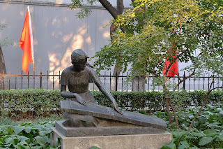 Sculpture of girl playing an instrument in park on Zheng Yi Lu in Beijing