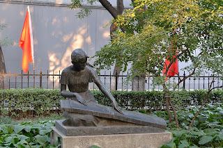 Sculpture of girl playing an instrument in park on Zheng Yi Lu in Beijing