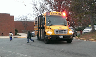 yellow school bus with flashing lights and kids getting off