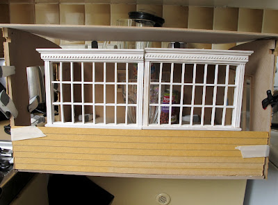 Mock up of a  dlls' house miniautre shed kit, with multipane windows propped up along the front wall.