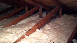 rolls of fiberglass insulation in attic