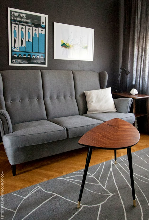 mid century modern living room with grey strandmon sofa and dark grey black wall - Petite Apartment