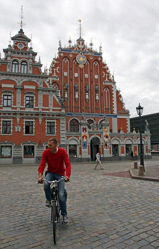 Foto do edifício na praça. Uma mulher a caminhar e um ciclista em primeiro plano