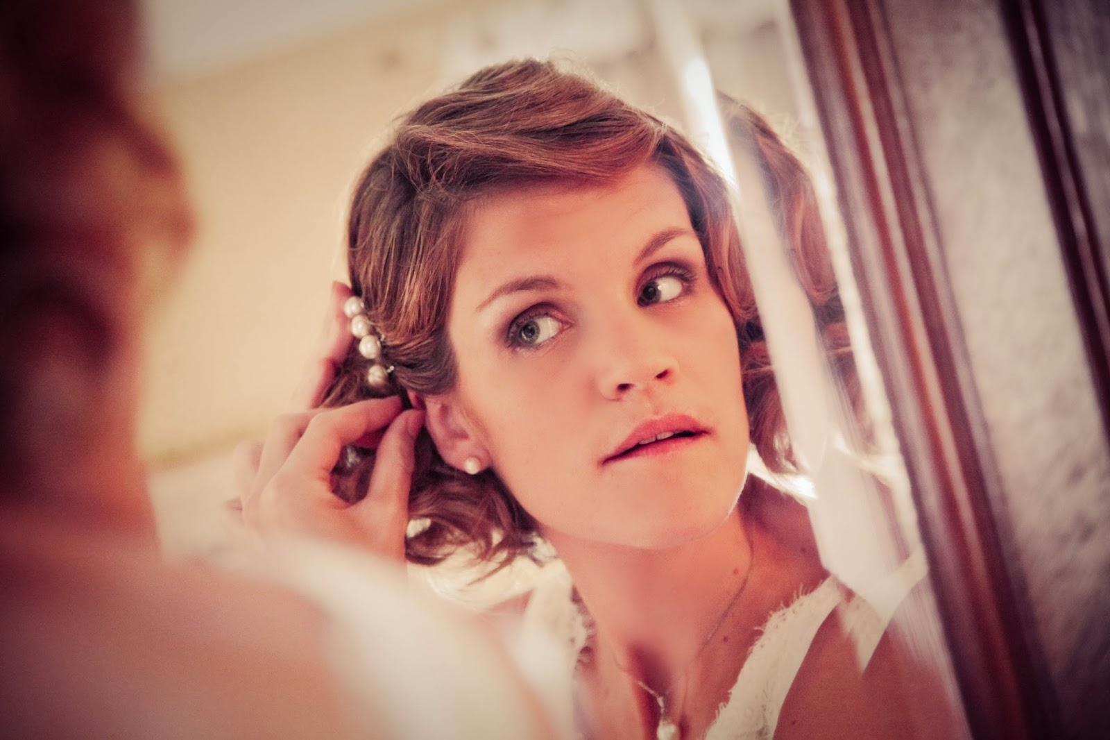 Bride getting prepared in front of a mirror