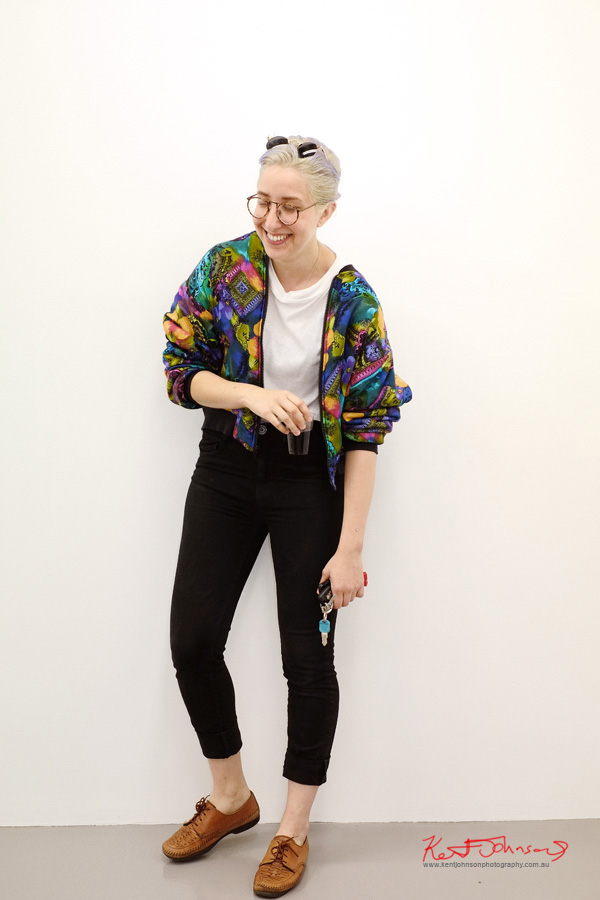 Two pairs of glasses, bright patterned multi coloured bomber jacket, white tee, black jeans brown shoes no socks and jewellery piercings on arms. Photographed with the Fujifilm X-Pro1