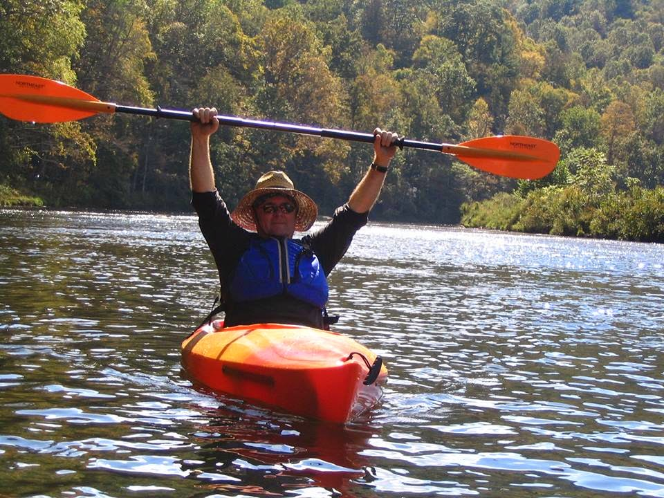 Ron holds his paddle above his head as he kayaks down the river.