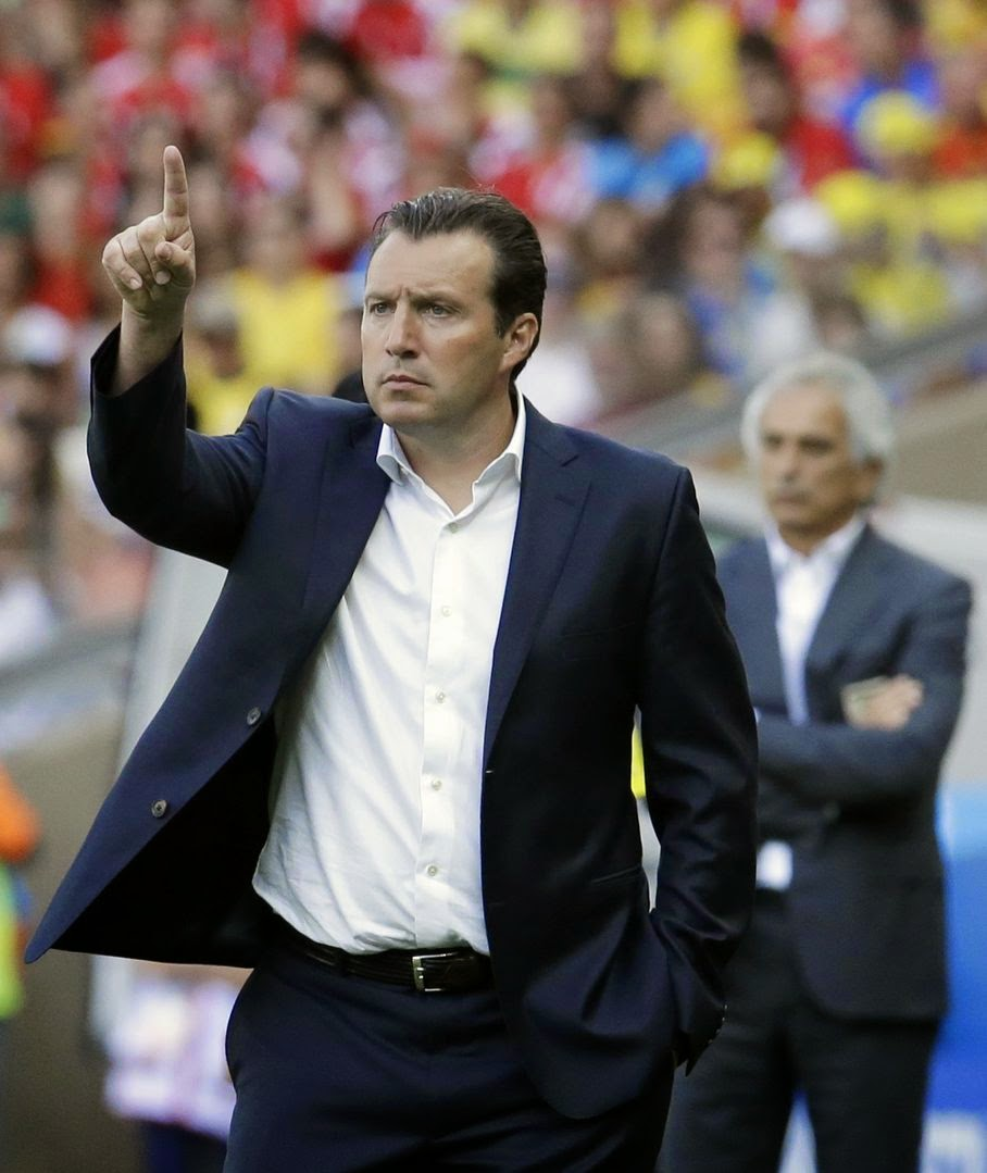 Belgium's head coach Marc Wilmots gestures as Algeria's head coach Vahid Halilhodzic looks on at rear during the group H World Cup soccer match between Belgium and Algeria at the Mineirao Stadium in Belo Horizonte, Brazil, Tuesday, June 17, 2014.