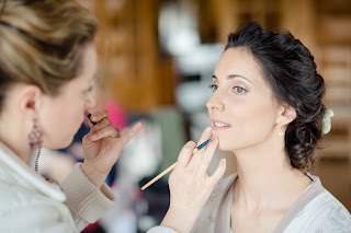 bride having her makeup done on her wedding day