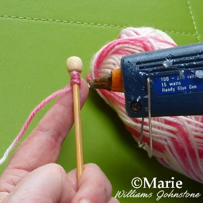 Attaching yarn to a wooden stick with a glue gun