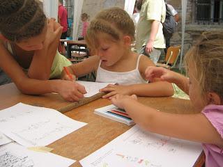 Három szöszke kislány ül az asztal mellett. Kettőnek közülök gyönyörű körbefont haja van. Testvérek. A nagy segít a kicsinek a játszólapok szöveges részeinél.