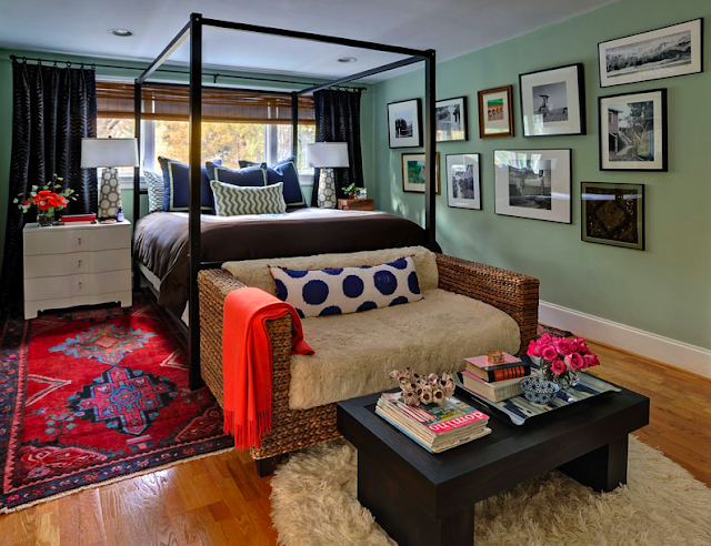 furbish studio, seating area at foot of bed, couch and coffee table at foot of bed, bedroom, coffee table, couch at foot of bed, interiors, interior design, interiors inspiration, rattan couch, ikat pillow, shearling rug, orange throw, canopy bedframe, coffee table vignette, pink roses