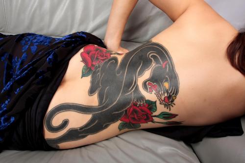 mujer acostada lleva tatuaje de pantera con una rosa en la espalda