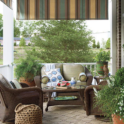 This cozy front porch decor is welcoming and warm with dark wicker furniture and plush pillows