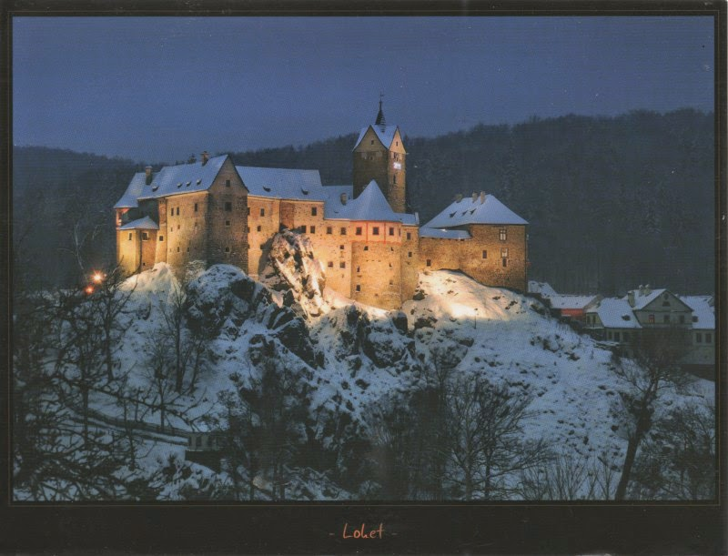 Medieval castle on hill, covered in snow, floodlit at night