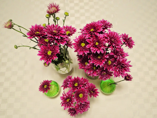 purple flowers arranged in multiple vases