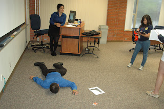 Students investigate a mock murder scene at the College.