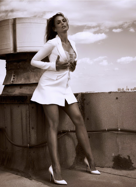 Cindy Crawford on a roof posing in a short white mini dress