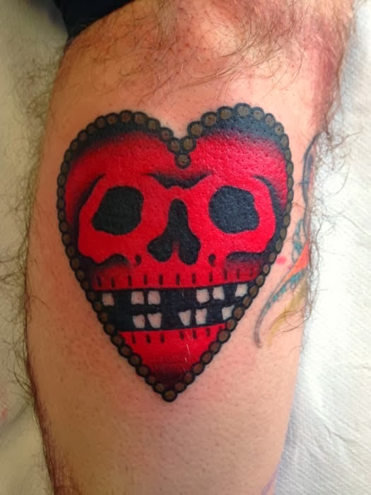 Red heart & skull leg tattoo.
